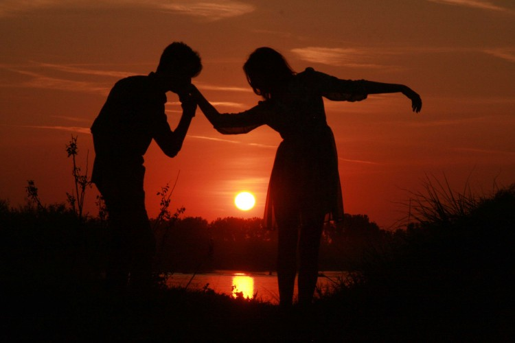 love couple kissing on hand at sunset