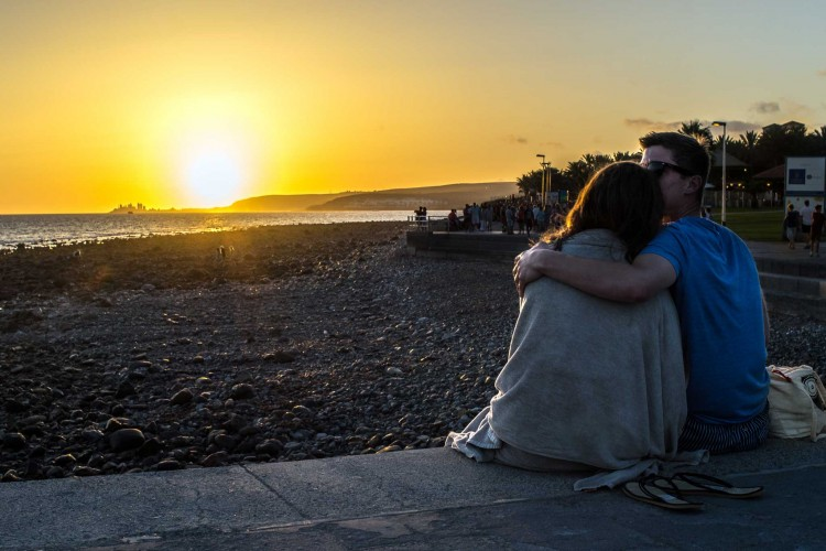 sweet couple kissing at sunset