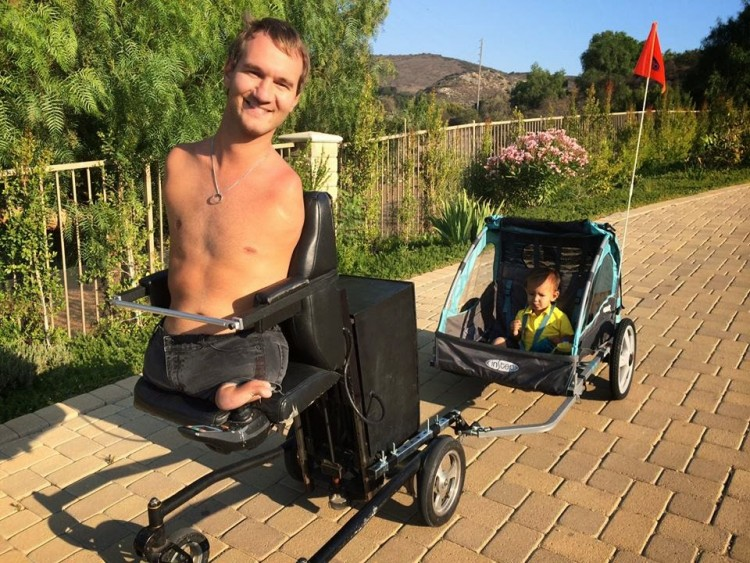Nick Vujicic Limbless motivational speaker takes his son out for a roll