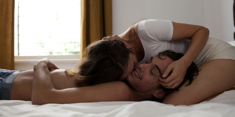 Couple in bed laughing and cuddling