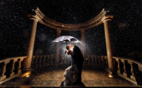 Newly Married couple kissing in rain