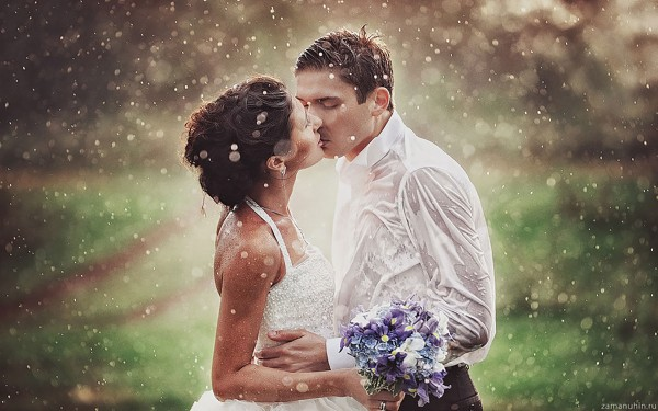 Passionate kiss of married couple in rain
