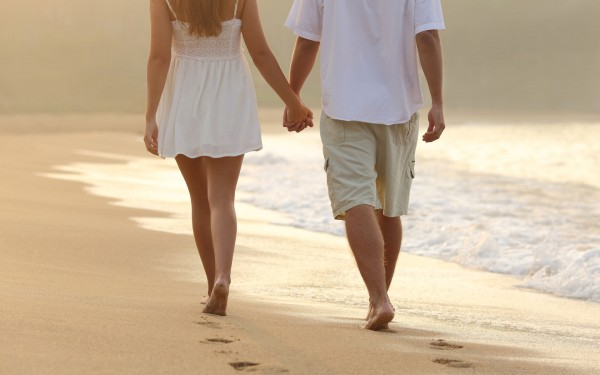 cute couple holding hand walking in seashore