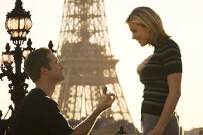 a young caucasian man proposes marriage to his girlfriend at the eiffel tower in paris